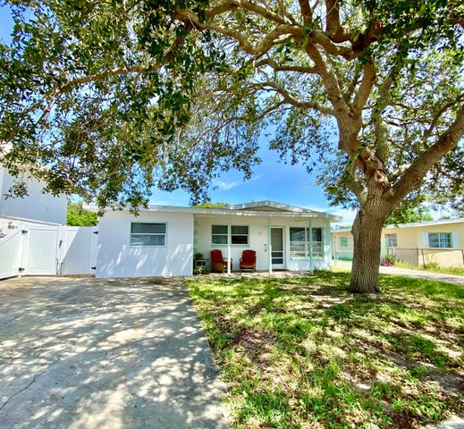 FOUR Blocks to the beach! This 3 Bedroom home is brilliantly situated within steps to Public Beach Access, 1/2 mile to Banana River, 2 Miles to Port Canaveral, and 4 miles to Cape Canaveral Spaceport.Fully Fenced level lot features dual driveways, Detached 675 SQFT Garage/Workshop with Electric, Covered Porches and Shaded Pavilion.The Open Floor-plan features large windows, vaulted ceilings, fresh ceramic tile throughout. Kitchen has been recently updated with granite counters, recessed lighting, and appliances. Updates continue in fixtures, Venetian Blinds, Interior Paint and more! Roof was installed in 2017. The large third bedroom can be secured from main home and has short term rental possibilities with private entrance and separate driveway.Come see today!