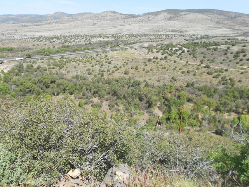 This is a valuable 54+ acre site directly along side I-17 and Highway 169 with interior wooded acreage alongside Cienega Creek.  The site, outside of city limits and regulated by Yavapai County, can have varied uses according to the adaptable zoning. Uses can include a truck stop, winery or home construction. The interior views are wonderful and includes one boundary on Ceniga Creek.  Water in the area has been abundant for previous wells. BRING ALL OFFERS & POSSIBLE OWNER FINANCING WITH GOOD TERMS. Call for a tour of this one of a kind property or for more information.
