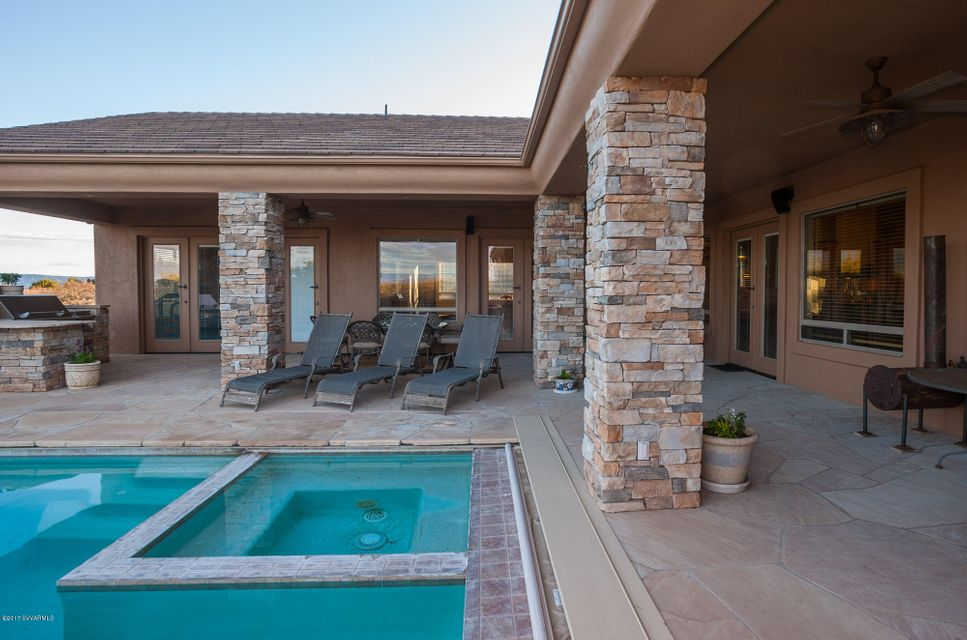 Absolutely stunning home with breathtaking panoramic views of the Verde Valley, Sedona Red Rocks, San Francisco peaks and Mingus Mountain. This is an incredible home for entertaining with a negative edge pool and Hot Tub, Built in Barbeque and it backs to forest service. This custom, one owner home has tons of custom features. On the main level you walk into a home with soaring cathedral ceilings an open split floor plan with formal & informal living room and dining room areas, 4 bedrooms, a chiefs kitchen with high end appliances to include a subzero refrigerator, office, game room or in-law suite with a wet bar and workout room.  On the lower lever there is a theater room, huge custom wine cellar, 8 X 16 vault, wet bar and another family room with an outside entrance and so much more.