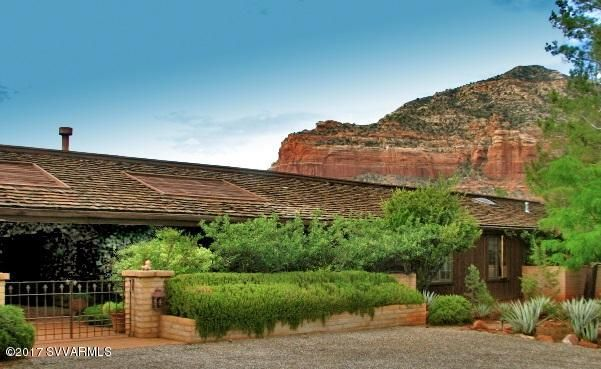 One of a kind, classic Sedona styled home on 7.5 acres in town. Don Woods design, saltillo tile in main living areas with huge living, dining, family rooms, library, separate elegant guest suite. Enjoy panoramic views from the large deck that wraps around to pool area.  Master suite is fantastic with his & hers closets, huge dressing area, a refreshment center, exercise room.  Greenhouse, dog run.