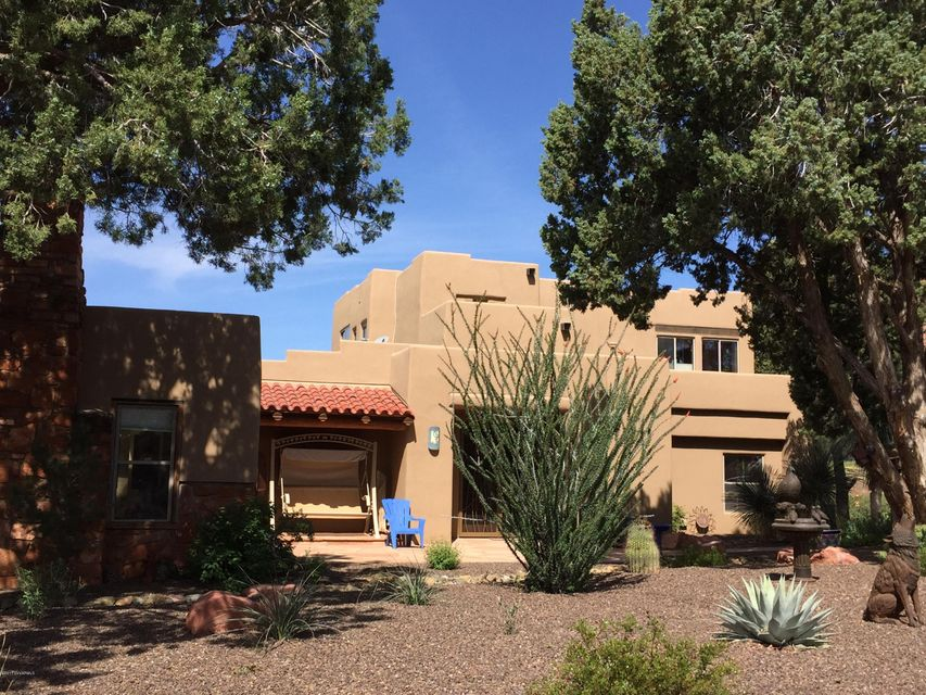 Rare Sedona Ranchette. $137K below appraisal and market value.  Unblockable views! Lee Mtn. Valley is a small, peaceful scenic area, no thru traffic. Santa Fe style, using warm tones, interior wood trim & tiles & high ceilings. Can easily be converted to 3 master suites. 3 indoor fireplaces & 1 kiva.  Master ste 980 Sq Ft with sitting room & deck.Views in all directions. Cab/Sav wine producing vines and organic garden. Up to 8+ horses.  No CC&Rs. AMPLE parking. Zoned for a guest house. The media room is an historical rock structure dating to 1947, one of the oldest in the Big Park area. Fenced for dogs. Low Maint. vegetation. Additional lot for sale 2.2 acres for $180 K, totaling 4.79 acres. So quite you can hear a pin drop and dark skies. 2.1 miles to stores. Motivated Owner/Age