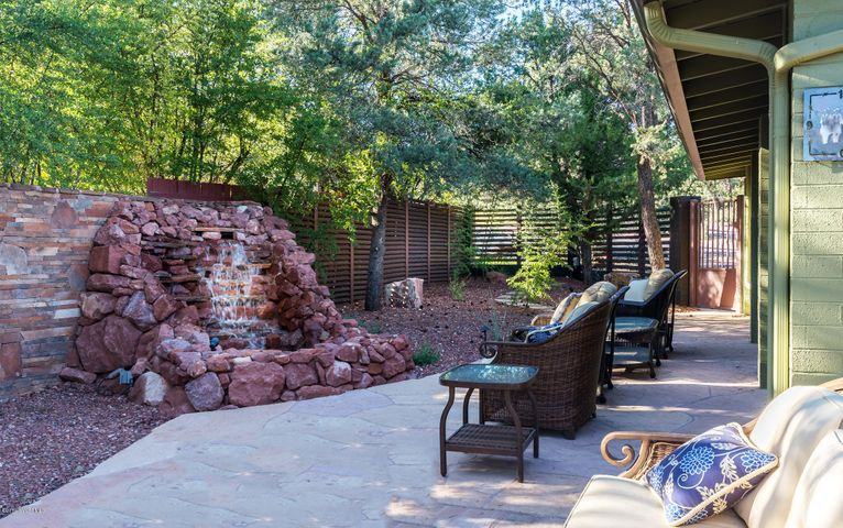 Outdoor seating surrounds the red stone waterfall and a fire pit.