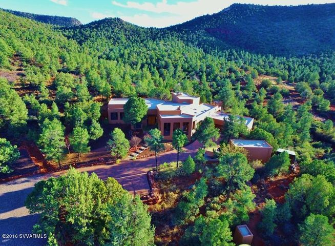 Aerial view of front of house with adjoining National Forest behind.