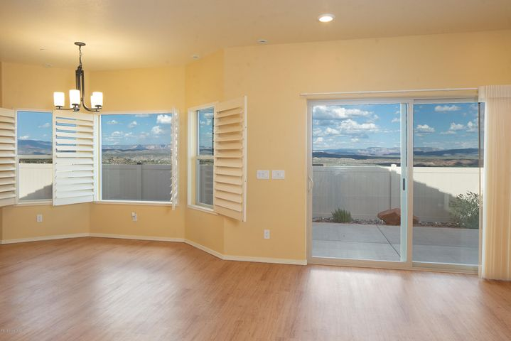 Spacious patio for easy outdoor living. Wood Shutters and Sheer Vertical Shades for the patio door.