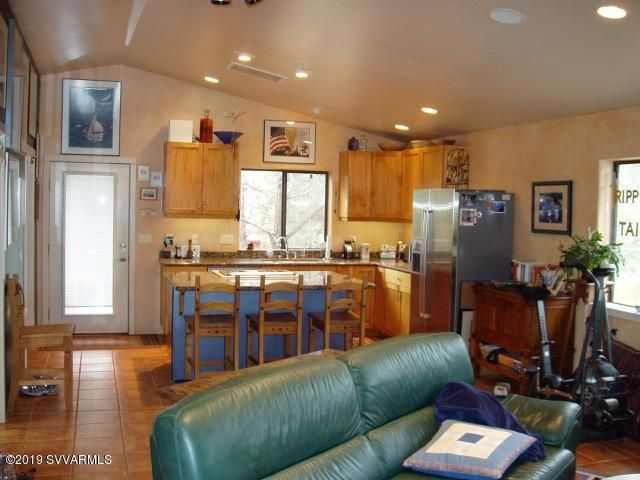 Windows all around with views. Open kitchen with breakfast bar, granite counters, gas range