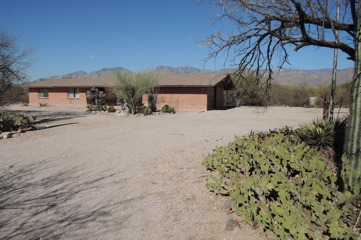 View from the driveway approaching the home from the south with panoramic Catalina Mountain views and heavily wooded acreage to the north and west side of the home.