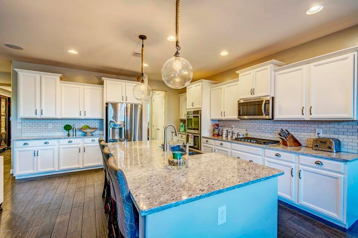 Tastefully upgraded to Gourmet kitchen, upgraded granite, and stainless steel appliances. Apron sink, extended wall of cabinets, upgraded cabinets, crown cabinet moldings, pots & pans drawers, built-in recyclable cabinets, upgraded SS appliances, upgraded lighting, beautiful ceramic wood-looking planks flooring.