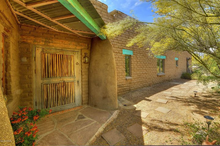 """Front of stabilized mud adobe hacienda layed with 24"""" solid walls. Sahuaro ribbed screen door/hand crafted front door"""