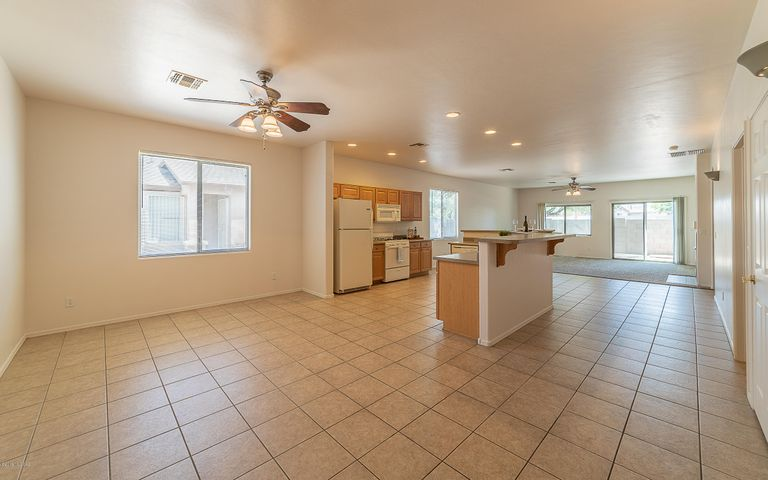 Two spacious living areas with lighted ceiling fans separated by kitchen. Mostly tile floors with brand new carpet in living room and fresh paint throughout.