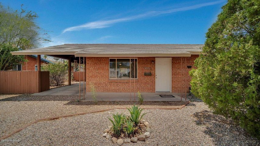 This lovely brick home has a carport visible at left as well as a long driveway for additional parking. Please notice the front door at right center and the mature landscaping.