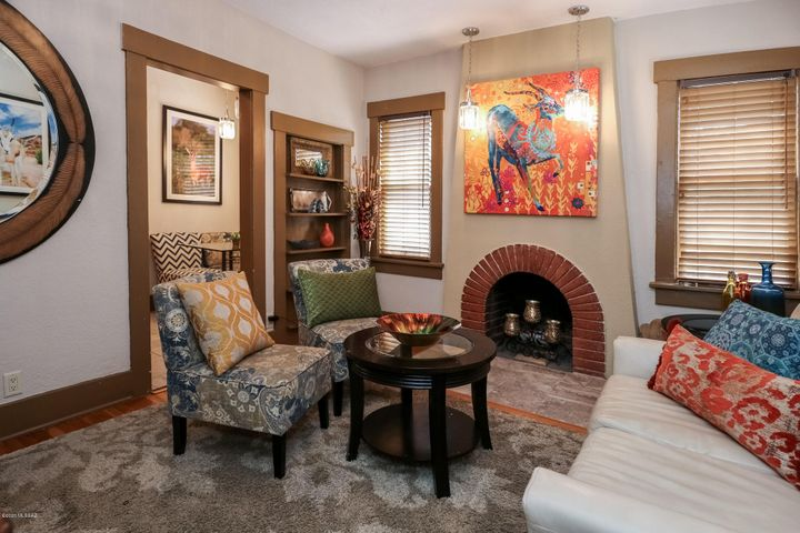Darling livingroom features original fireplace, doors, casings, original wood floors
